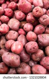 Heap of raw red potatoes in grocery bin