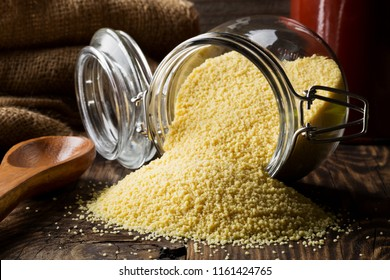 Heap of raw, uncooked couscous in glass jar on wooden table background