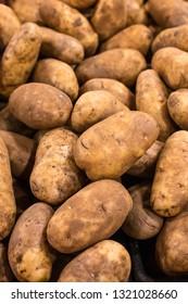 Heap of raw white potatoes in grocery bin