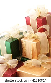 Heap of red, gold and green foil gifts on white background.