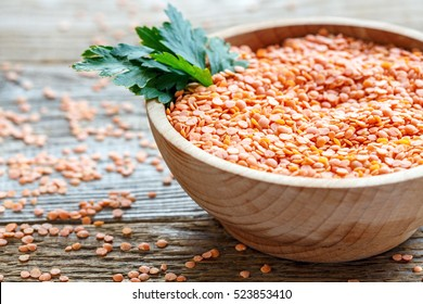 Heap of red lentils and parsley in a bowl on old wooden table.