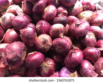A heap of red onion Red onions background red onion sold on fresh fruit panels in Thai fresh market Plenty of Onions sold in a market Fresh organic red onions in outdoor market