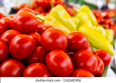 A heap of red tomatoes at market. Vegetables in background.