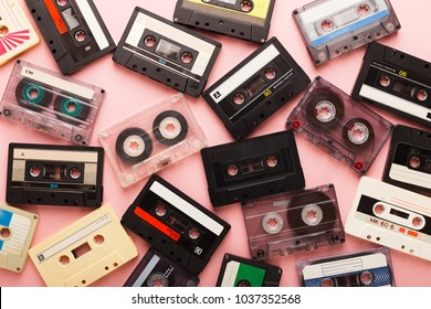 Heap of retro audio cassette tapes on pink background. Top view on vintage media devices, copy space, flat lay