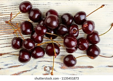 Heap of ripe cherries on vintage background. Fresh juicy berries on light wooden surface. Healthy summer fruit.