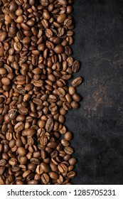 Heap of roasted coffee beans as border on vintage black background. Top view point.