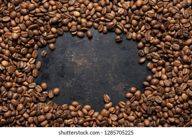 Heap of roasted coffee beans as frame on vintage black background. Top view point.