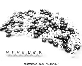 heap of round letters black and white and news word written in danish; nyheder