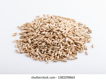 Heap of rye grains isolated on white background. close up, selective focus, side view.