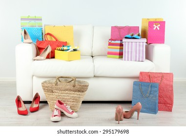 Heap of shopping bags with boxes and shoes on sofa in room