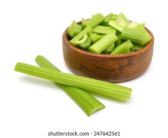 heap of sliced celery in wood bowl, isolated on white background