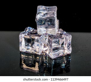 Heap of a small white and transparent ice cubes isolated on the black background reflecting