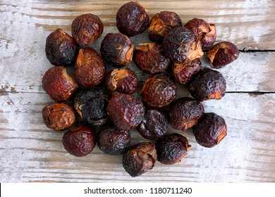 Heap of soap nuts on wooden background. Close-up.