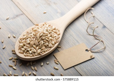 heap of spelt in wooden spoon on table with label for text.