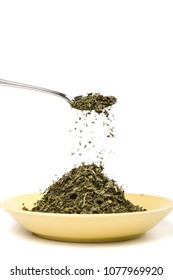 Heap and spoonful of dried herb on white