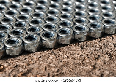 Heap of stainless screw-nuts on wooden background. Background