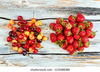 Heap of strawberries and cherries, top view. Ripe berries on vintage wooden background. Fresh from garden.