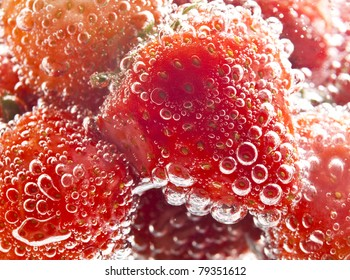 heap of strawberries in water with bubbles