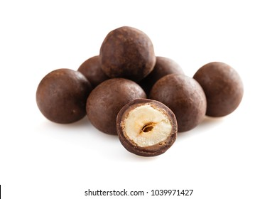 Heap of sugared hazelnuts dragees in chocolate isolated on white background. Handmade chocolate balls candies filled with nuts