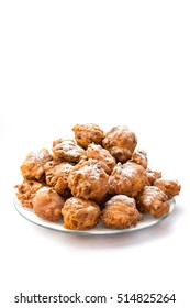Heap of sugared oliebollen or fried fritters on glass dish isolated on white background