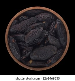 heap of tonka beans  in wooden cup isolated on black background. top view
