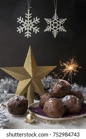 heap traditional Dutch oliebollen, oil dumpling or fritter, for New Year's Eve, with sparkler, golden Christmas stars, against black background