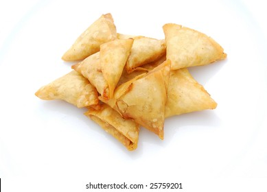 Heap of traditional South African Samoosa triangle pockets filled with chicken and beef mince isolated on white studio background.