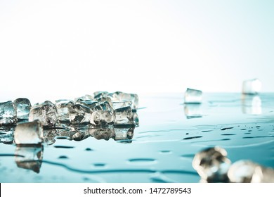 heap of transparent melted ice cubes with water puddles on emerald and white background