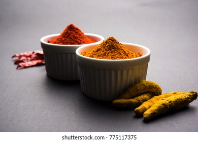 heap of turmeric and red chilli powder in a ceramic bowl on a white or black background