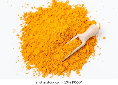 Heap of turmeric. Wooden scoop. Isolated on white. Top view.