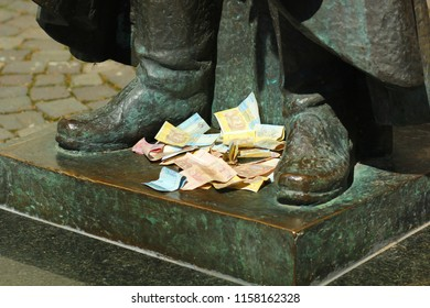 Heap of ukrainian hryvnas banknotes left at the feet of the bronze statue by turists for luck and returning
