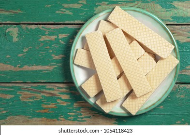 Heap of wafers in plate on old green wooden table, top view