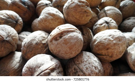 Heap of walnuts with peel. A large number of untreated walnut. Nuts for a sweet dish or cake.