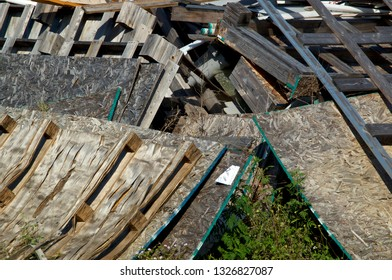 A heap of wooden pallets or skids and sheets of particle boards in a pile outdoors in sunlight.