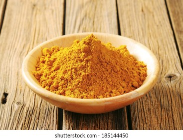 heap of yellow curry powder in the wooden bowl