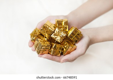heap of yellow gifts in the hands