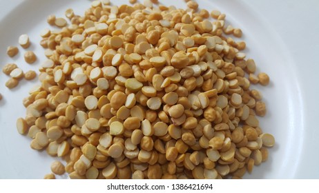 Heap of yellow split chickpeas in white plate background. Daal Chana is used as raw food in Asian countries like India or pakistan