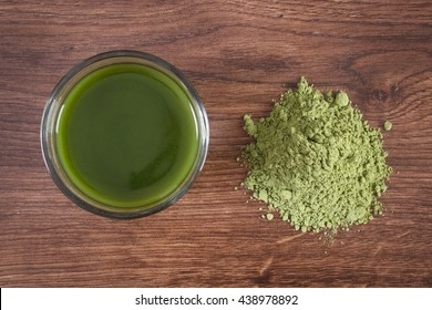 Heap of young powder barley with cup of beverage on wooden background, healthy nutrition and lifestyle, body detox
