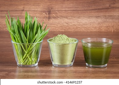 Heap of young powder barley, barley grass and beverage on wooden background, healthy nutrition and lifestyle, body detox