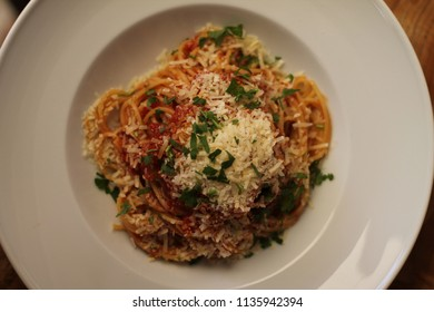 Heaped plate of delicious Italian spaghetti pasta with fresh basil leaves and grated parmesan cheese. Viewed low angle and top from the side on a wood table.