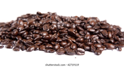 A heaping pile of cofee beans on white.