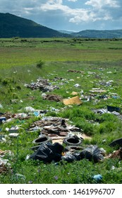 Heaps of garbage in the nature. Green grass and mountains on background. Ecology and waste collection concept.