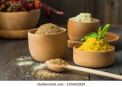Heaps of various ground spices on wooden background. Georgian