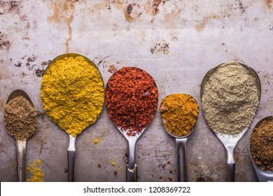 Heaps of various ground spices in spoon on stone  background. Georgian