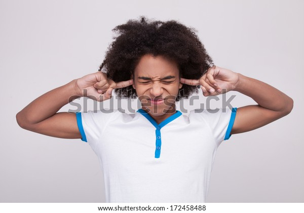 Hear no evil. Funky African teenager making a face and covering ears by fingers while standing isolated on grey background