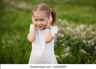 Hear no evil - Lovely little girl covering her ears with hands, doesn't want to hear anything, outdoors