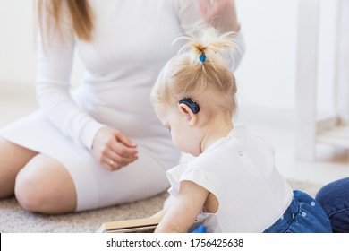 Hearing aid in baby girl's ear. Toddler child wearing a hearing aid at home. Disabled child, disability and deafness concept.