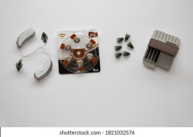 Hearing aids and accessories (batteries, domes and wax guards) isolated on white background. Maintenance of devices used to assist with hearing loss and sound. Batteries to be changed weekly - Shutterstock ID 1821032576