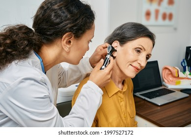Hearing exam for elderly citizen people. Otolaryngologist doctor checking mature woman's ear using otoscope or auriscope at medical clinic