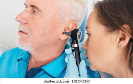 Hearing exam. Elderly patient during a hearing test, a doctor with an otoscope checking the hearing of an elderly patient, close-up